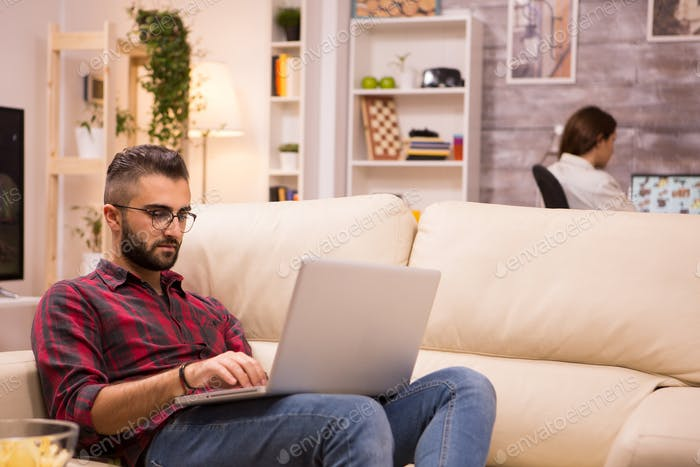 Young entrepreneur working on laptop sitting on sofa