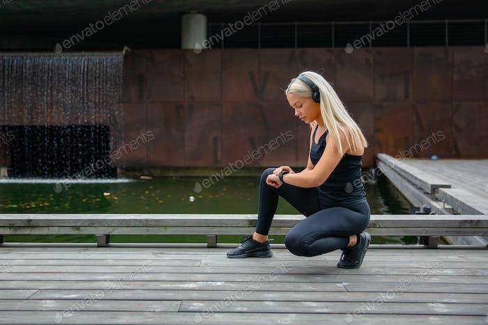 Beautiful fitness woman using smart watch phone