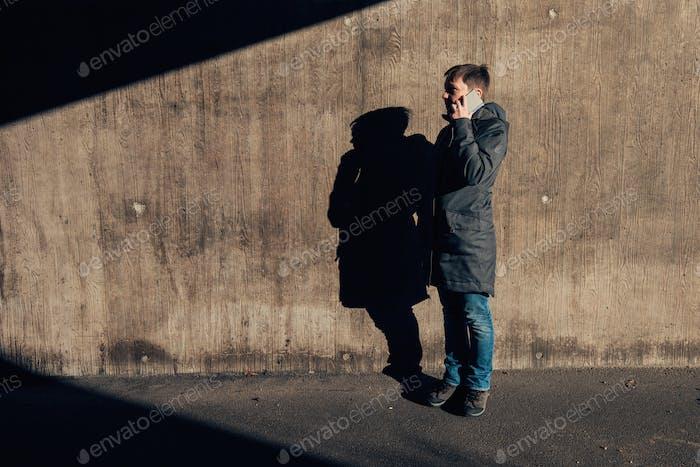 Ernsthafte authentische Frau im Gespräch auf dem Handy auf der Straße