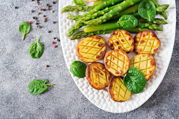 Halves of baked potatoes and asparagus. Dietary menu. Healthy food.