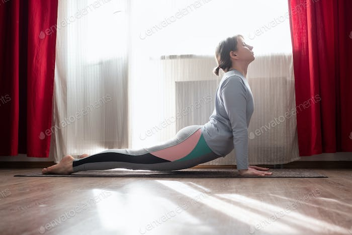 Young woman practicing yoga, doing urdhva mukha svanasana, upward facing dog