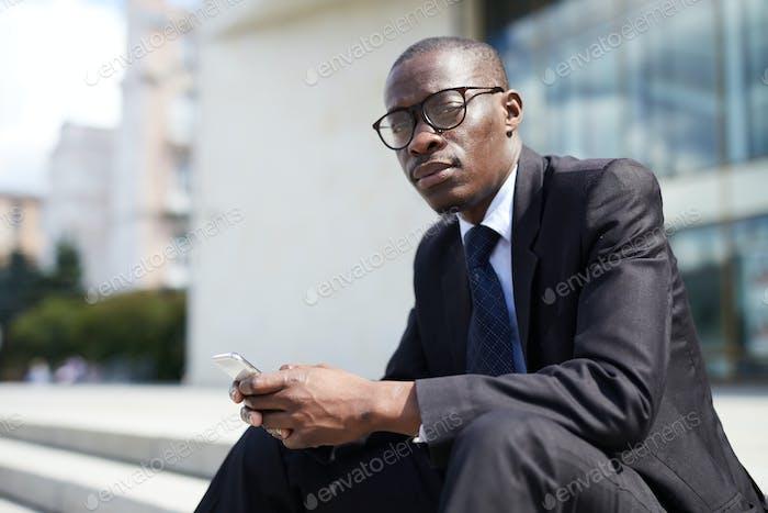 Afroamerikanischer Geschäftsmann sitzt auf der Treppe