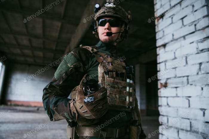 Military man ready to pull a check and to throw a smoke grenade at the building during combat