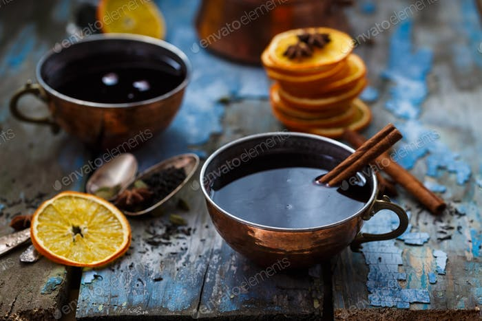 Grog in copper cups with spices and orange slices