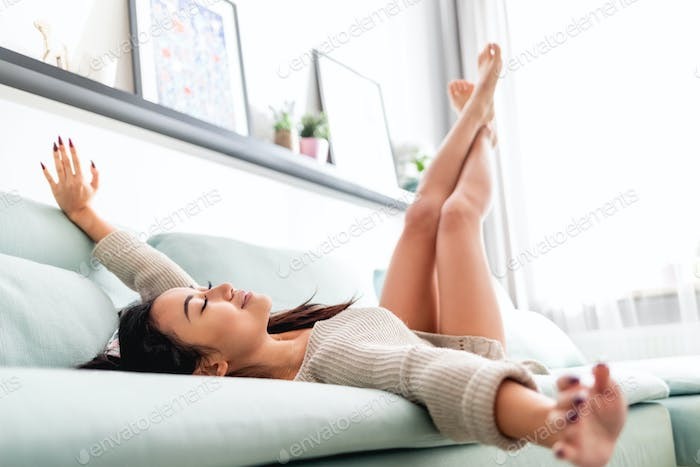 Leisure time at home, asian woman in positive mood relaxing on sofa