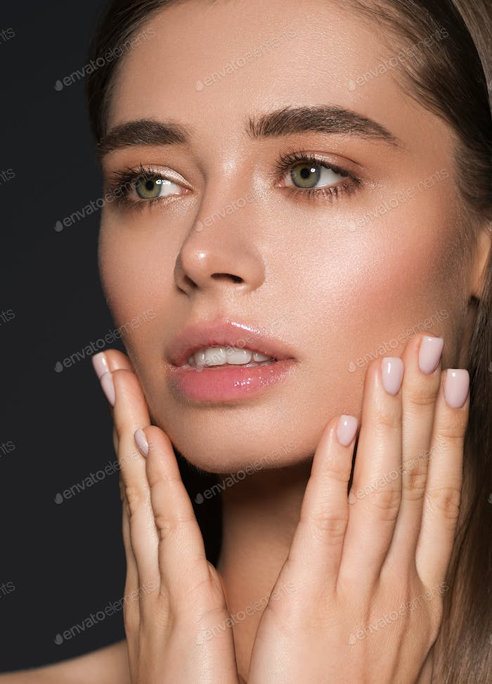 Woman beauty face hands fingers manicure touching close up over dark