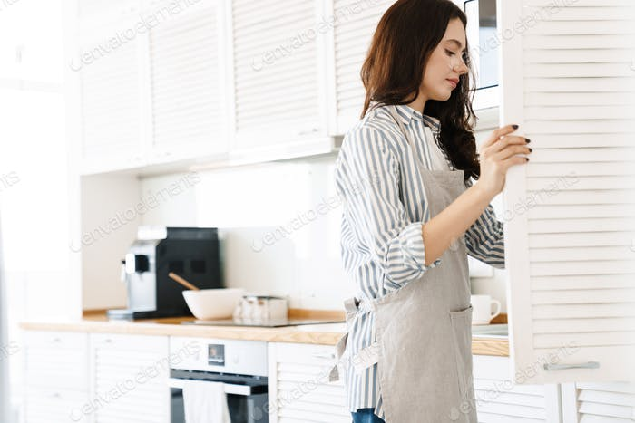Image of focused young woman opening cupboard while cooking pie