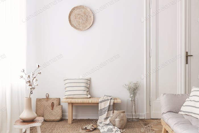 Flowers on wooden table near bench with pillow and blanket in wh
