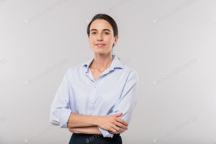Happy young elegant businesswoman with arms crossed by waist looking at you