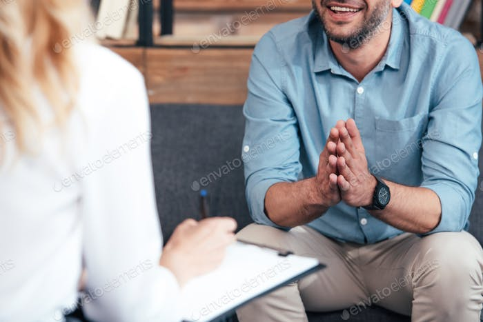 cropped image of female counselor writing in clipboard and smiling male holding hand palms together