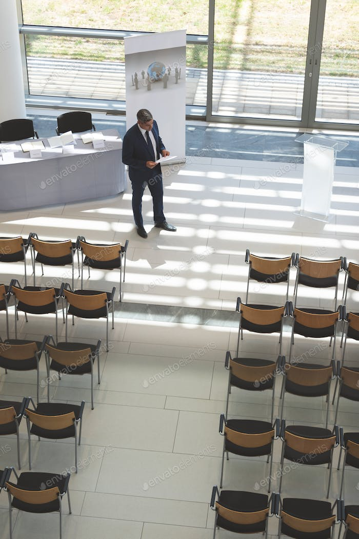 Businessman practising speech in empty conference room in modern office building