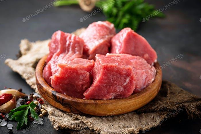 Rohes gehacktes Fleisch mit Gewürzen auf rostigen Hintergrund