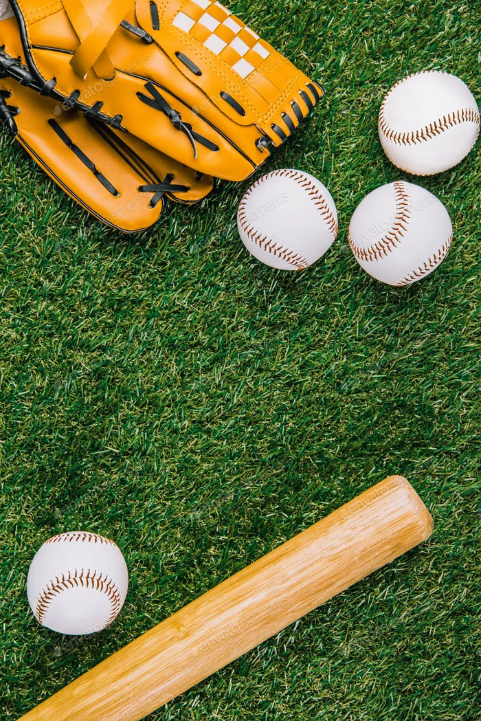 flat lay with baseball equipment arranged on green grass