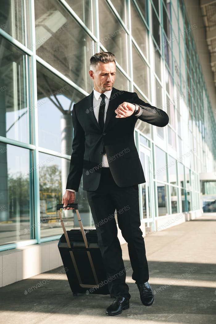 Confident businessman dressed in suit walking