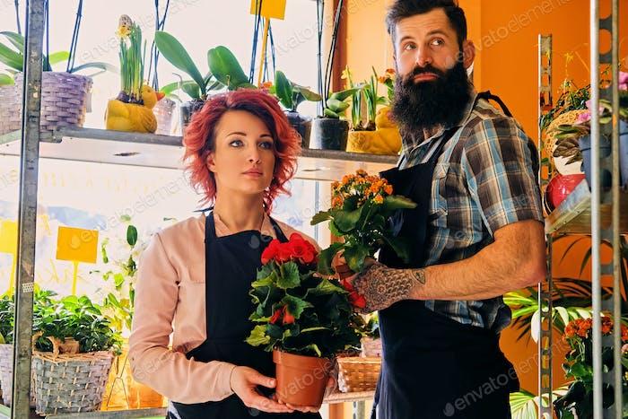 Rothaarige weibliche und bärtige tätowierte männliche Verkauf von Blumen in einem ma