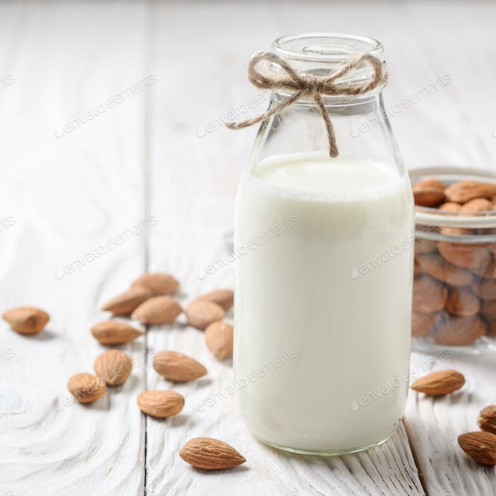 Milk or yogurt in glass bottle on white wooden table with almond