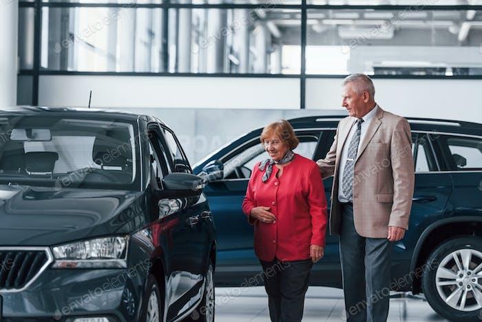 Alter Mann in formeller Kleidung, der die Frau bei der Auswahl des Automobils unterstützt