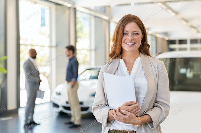 Satisfied saleswoman in car dealership