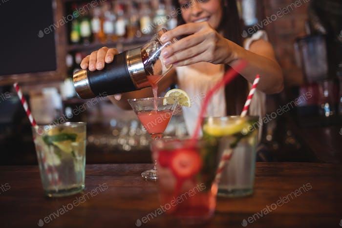 Довольно бармен наливает коктейльный напиток в стакане