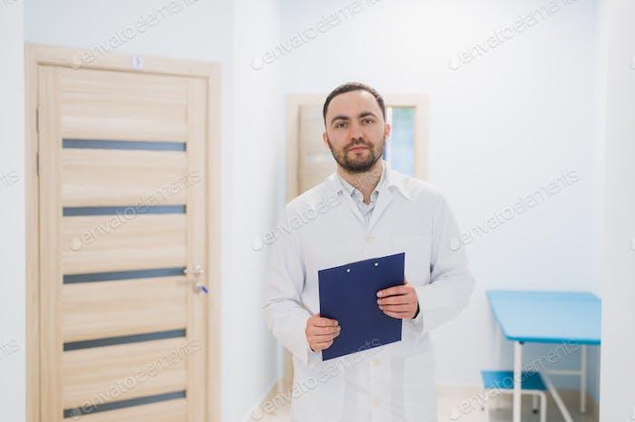 Fröhlicher junger Arzt hält eine Zwischenablage und Gesten mit der Hand in Krankenhausstation