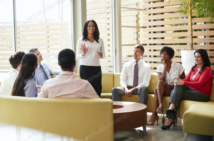 Colleagues listening to presentation by a female manager