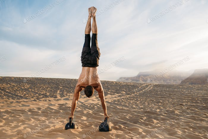 Male athlete stands on hands in desert