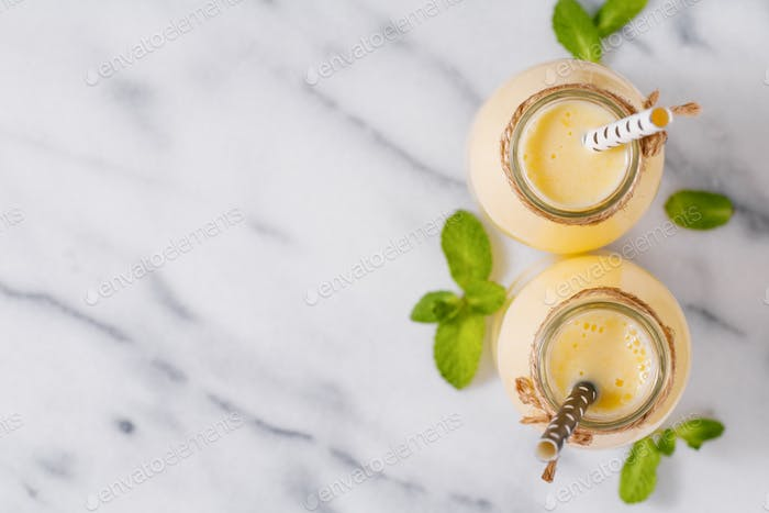 Top view of yellow fruit smoothies in the glass bottles with straw on the white marble