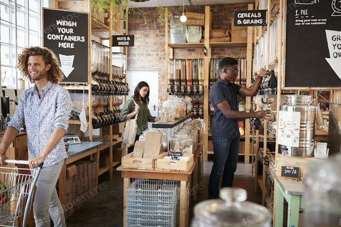 Shoppers In Dried Goods Section Of Sustainable Plastic Free Grocery Store