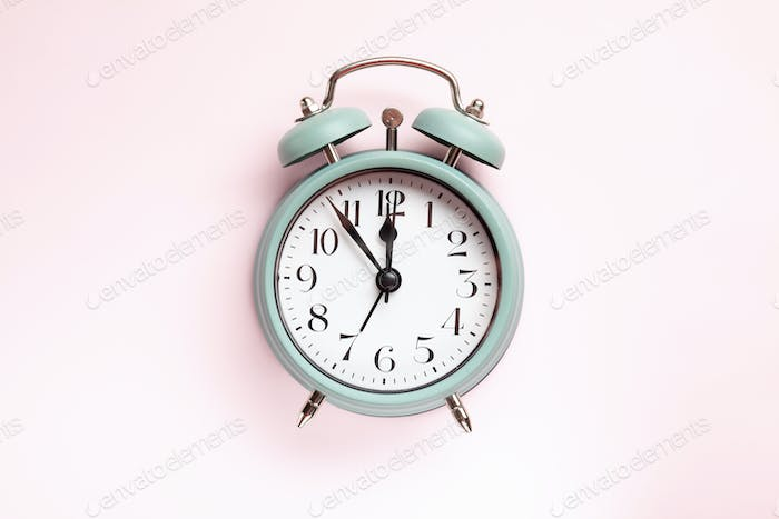 Retro style alarm clock over the pink background