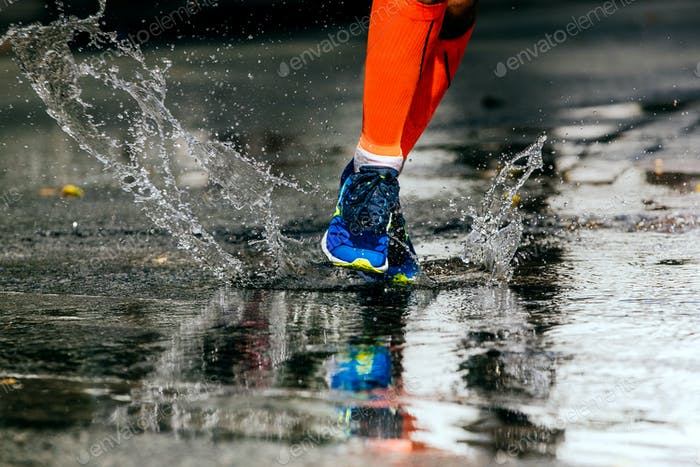 Sportlerläufer laufen auf Pfütze