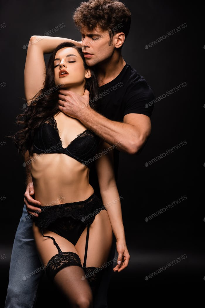 seductive man holding neck of sexy woman in black lingerie on black