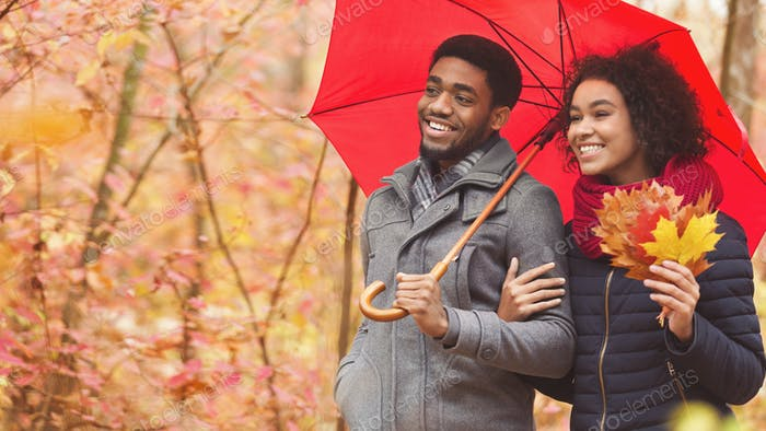 Happy afro couple walking under umbrella at rainy autumn day
