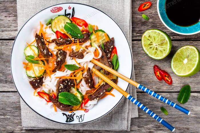 Lamb noodle salad with cucumbers, carrots, chili peppers and mint