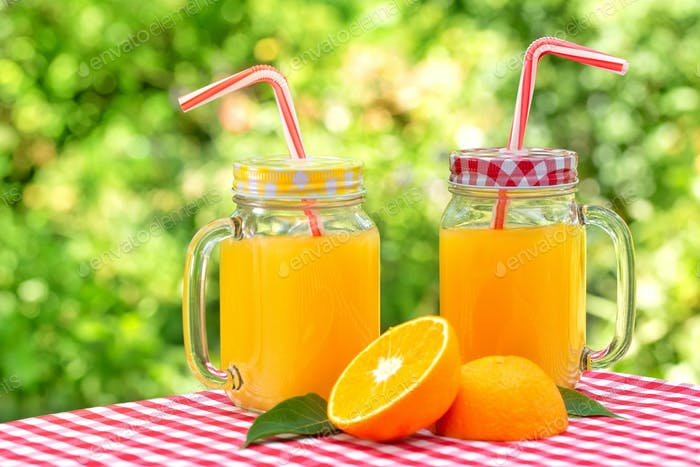 Two jars of orange juice on red checkered tablecloth