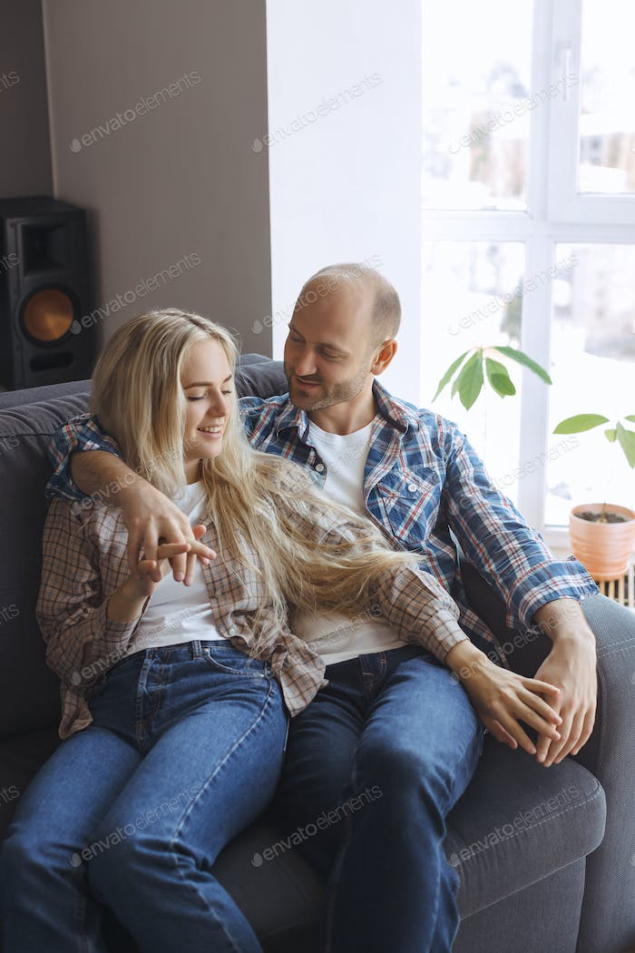 Couple Embracing Resting on Sofa at Home