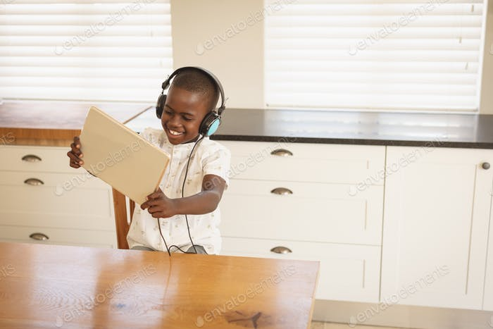 Front view of African American boy playing game on digital tablet at dining table in kitchen at home