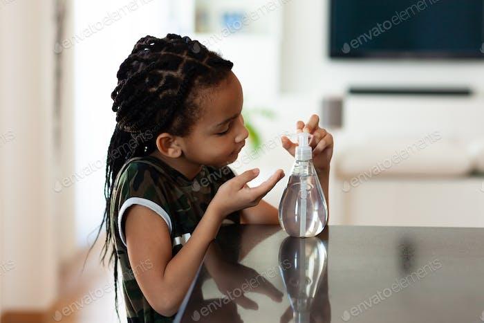 Schwarzen afroamerikanische Kinder, die antibakterielles antiseptisches Händedesinfektionsgel verwenden