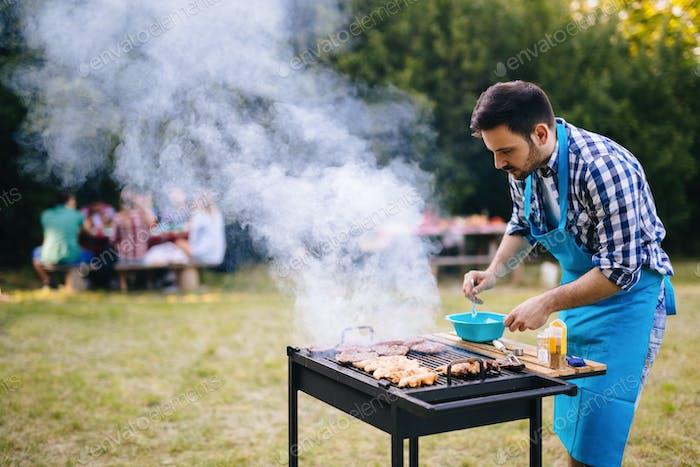 Glückliche männliche Vorbereitung BBQ Fleisch im Park