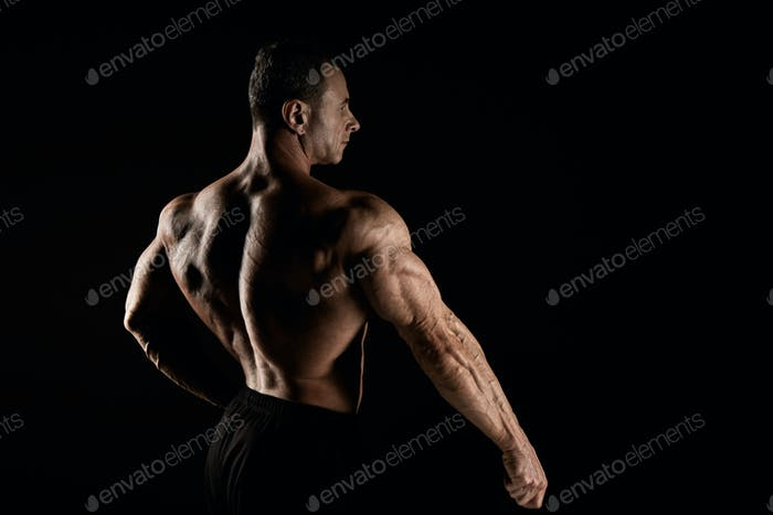 torso of attractive male body builder on black background.