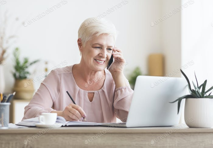 Smiling elderly lady talking to business partners