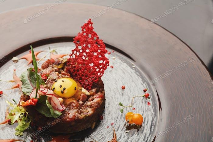 Modern restaurant dish. Veal tartare with quail egg closeup