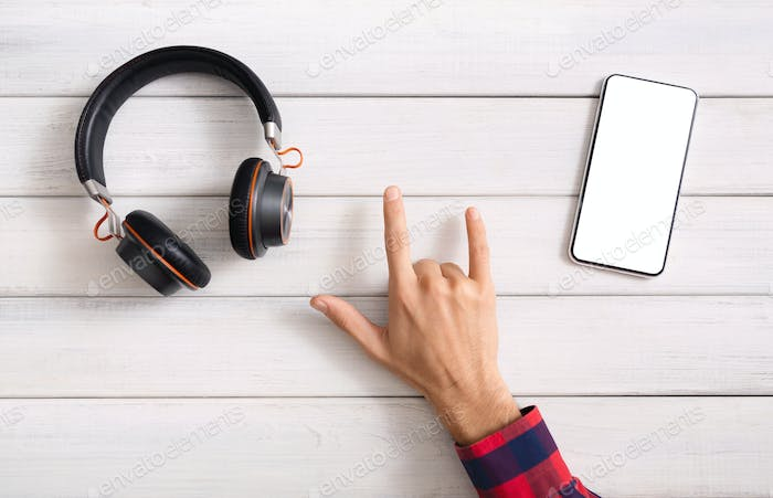 Man's hand making rock gesture between headphones and smartphone