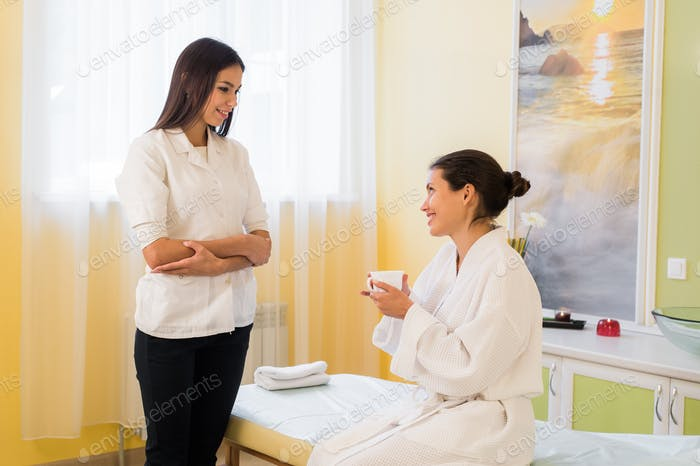 Pretty young woman wearing robe and masseuse talking after massage in a spa drinking some tea