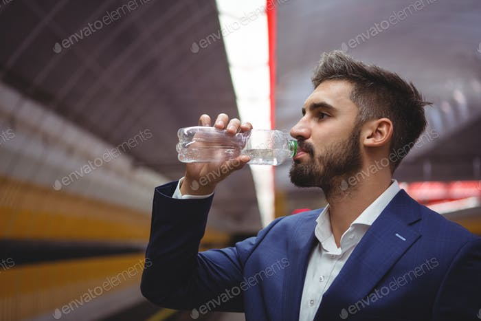 Business executive drinking water