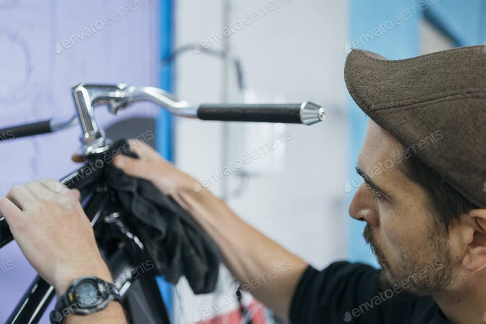 Bearded man cleaning bicycle