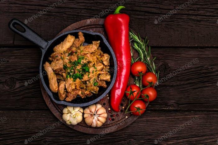 Gebratenes Schweinefleisch in einer Pfanne und Gemüse