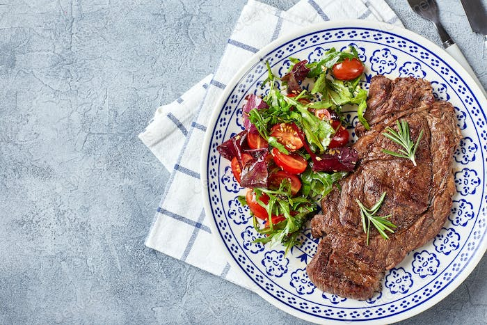 Grilled steaks and vegetable salad on light background. Table setting, food concept