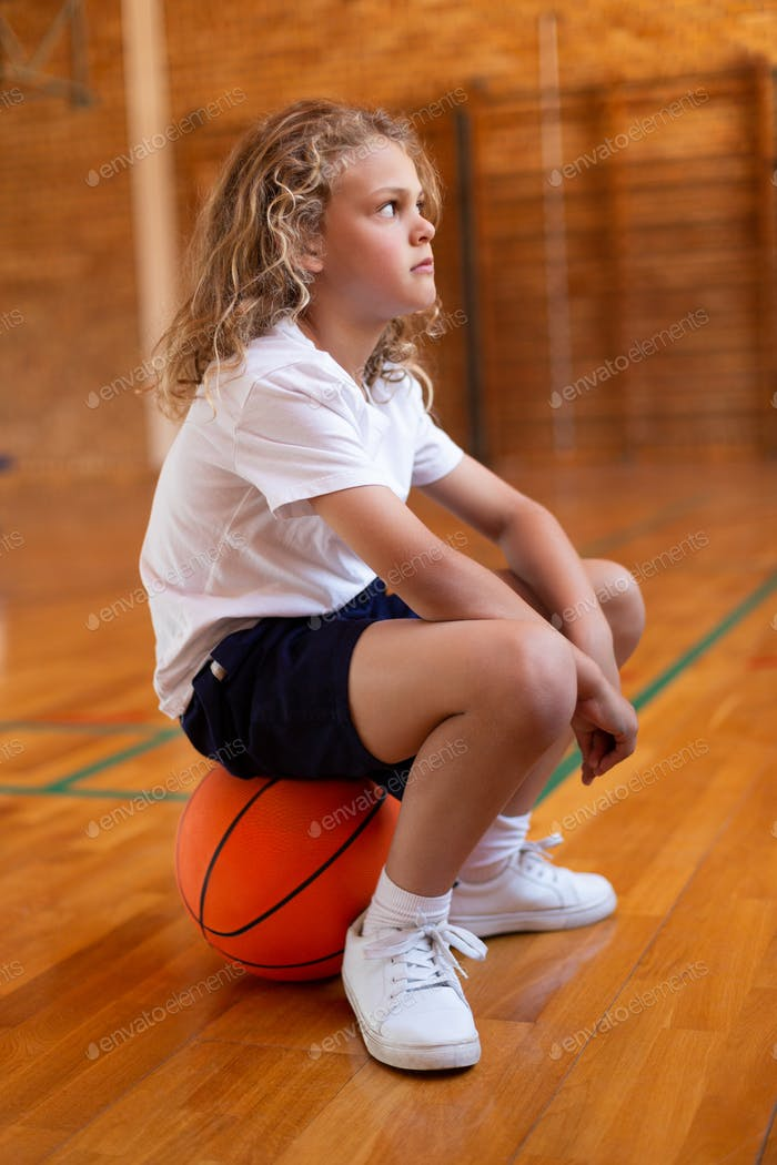 Side view of a mixed -race schoolgirl sitting on a basketball in basketball court at school