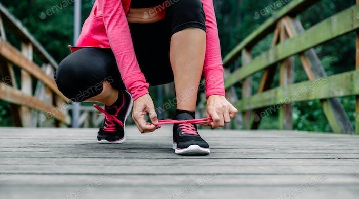 Sportlerin, die Schnürsenkel binden, die sich darauf vorbereiten zu