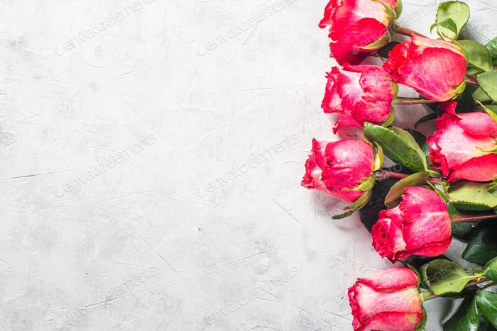Rote Rosenblumenstrauß auf Steintisch.